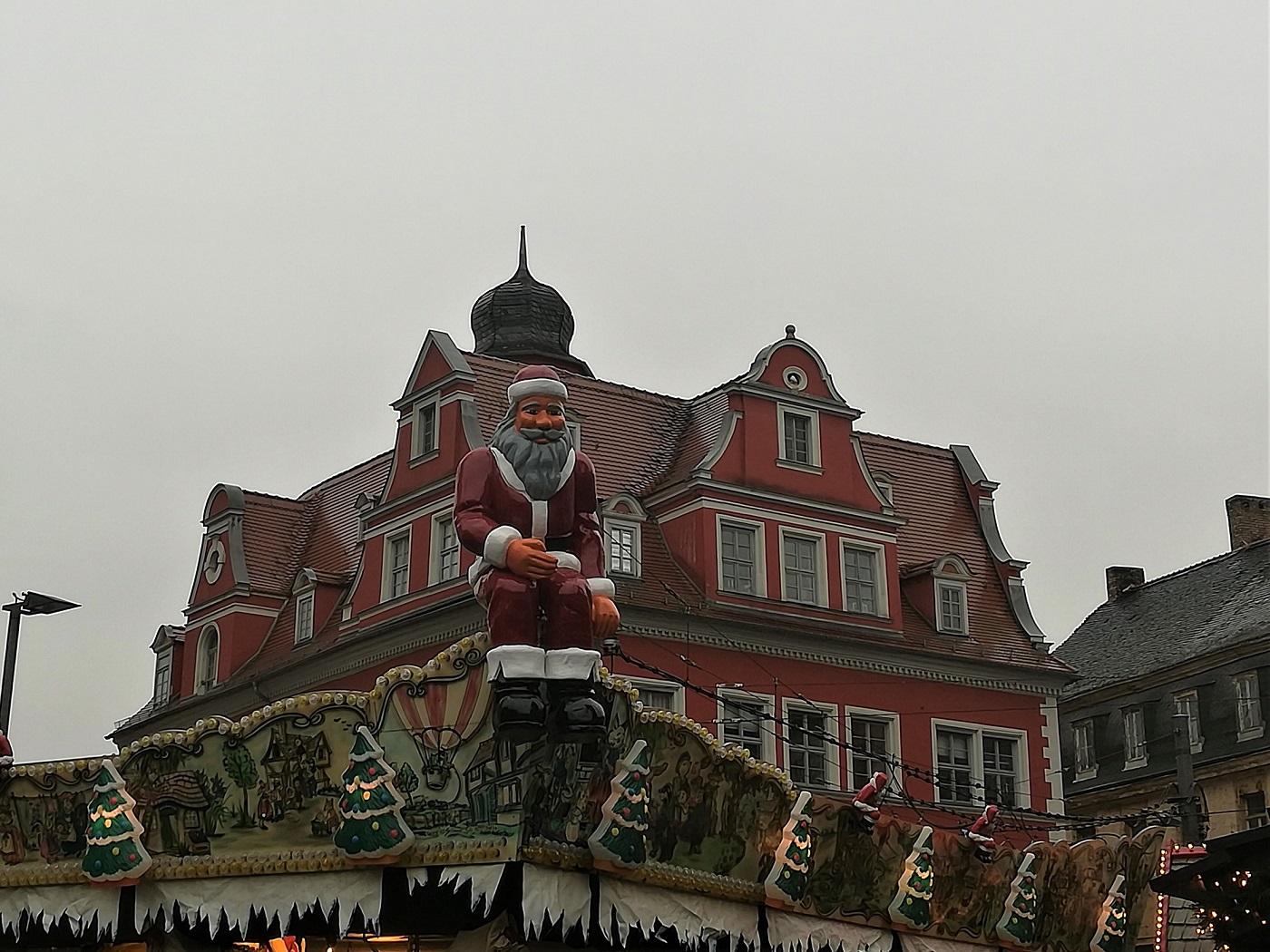 Weihnachtsmannfigur sitzt auf dem Dach eines Karussells