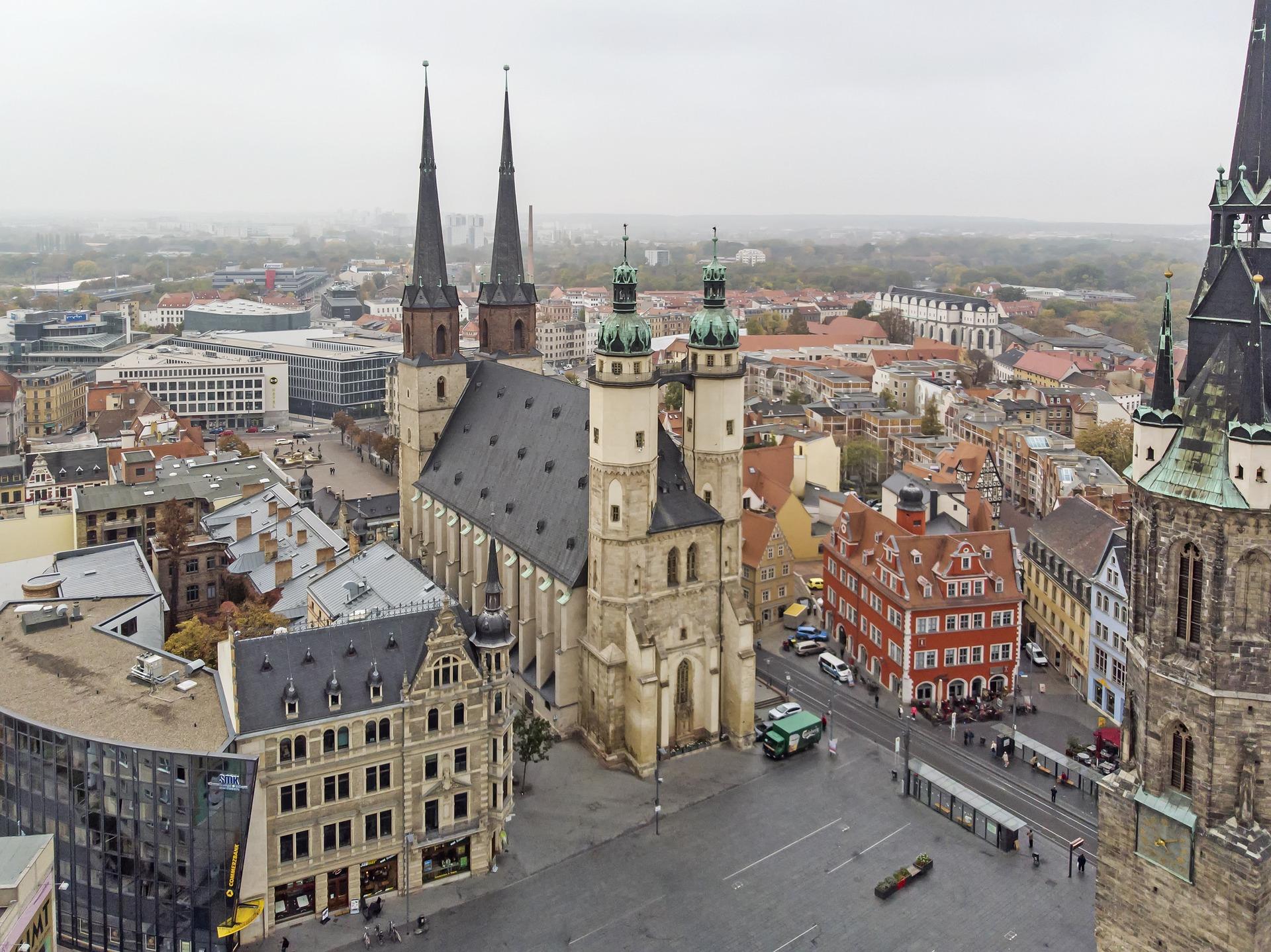 Die Marktkirche (li) mit Stadtschlösschen (rot, Mitte) und Rotem Turm (rechts), Marktplatz in Halle (Saale).